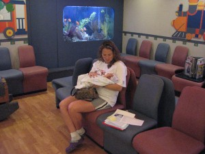 Mama is holding me in the waiting room with trains, fishes and neon lights!